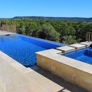 Ejemplo de piscinas y jacuzzis infinitos, contemporáneos, de tamaño medio, a medida, en patio trasero, con suelo de baldosas
