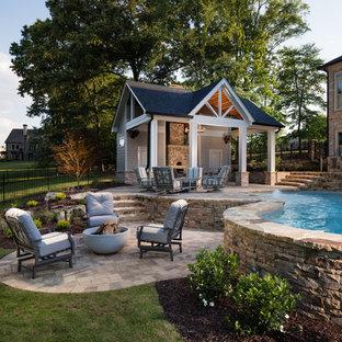 Imagen de casa de la piscina y piscina natural, clásica, grande, a medida, en patio trasero, con adoquines de hormigón