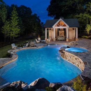Ejemplo de casa de la piscina y piscina natural, clásica, grande, a medida, en patio trasero, con adoquines de hormigón