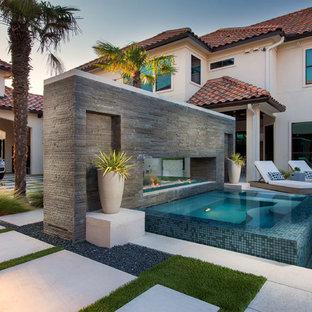 Ejemplo de piscina mediterránea, grande, a medida, en patio, con adoquines de hormigón