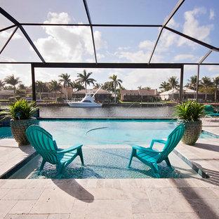 Mittelgroßer Maritimer Pool hinter dem Haus in rechteckiger Form mit Natursteinplatten in Miami