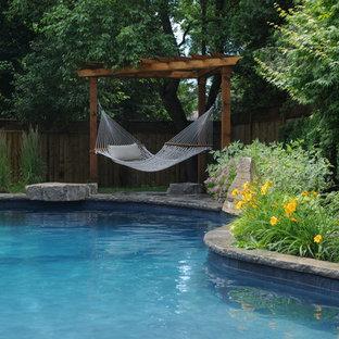 Foto de piscina con fuente clásica, de tamaño medio, en patio trasero, con adoquines de piedra natural