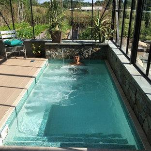 Modelo de piscina con fuente alargada, minimalista, pequeña, rectangular, en patio trasero, con entablado