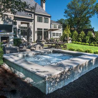 Esempio di una piccola piscina naturale classica rettangolare dietro casa con una vasca idromassaggio e pavimentazioni in pietra naturale