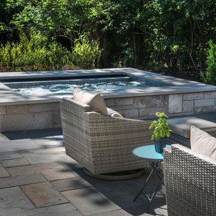 Foto di una piccola piscina naturale classica rettangolare dietro casa con una vasca idromassaggio e pavimentazioni in pietra naturale