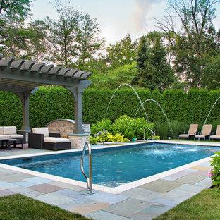 Klassischer Pool hinter dem Haus in rechteckiger Form mit Natursteinplatten und Wasserspiel in Chicago