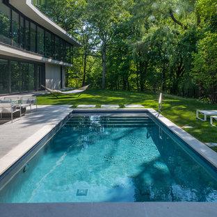 Modelo de piscina alargada, moderna, pequeña, rectangular, en patio trasero, con adoquines de piedra natural