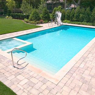Ejemplo de piscina alargada, clásica, pequeña, rectangular, en patio trasero, con adoquines de hormigón