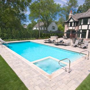 Modelo de piscina alargada, clásica, pequeña, rectangular, en patio trasero, con adoquines de hormigón