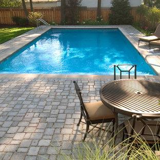 Imagen de piscina alargada, tradicional, de tamaño medio, rectangular, en patio trasero, con adoquines de hormigón