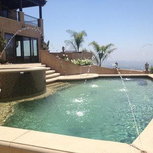 Ejemplo de piscina con fuente natural, contemporánea, de tamaño medio, a medida, en patio trasero, con suelo de hormigón estampado