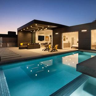 Ejemplo de piscinas y jacuzzis infinitos, actuales, de tamaño medio, rectangulares, en patio trasero, con adoquines de hormigón