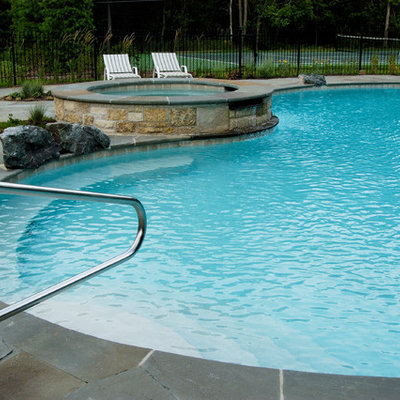 Example of a large mountain style backyard stone and custom-shaped natural hot tub design in Chicago
