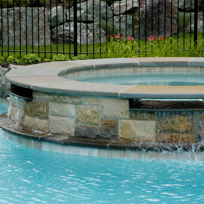 Example of a large mountain style backyard stone natural hot tub design in Chicago