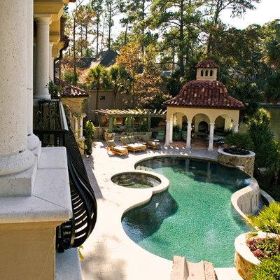 Large tuscan backyard concrete paver and custom-shaped lap hot tub photo in Atlanta