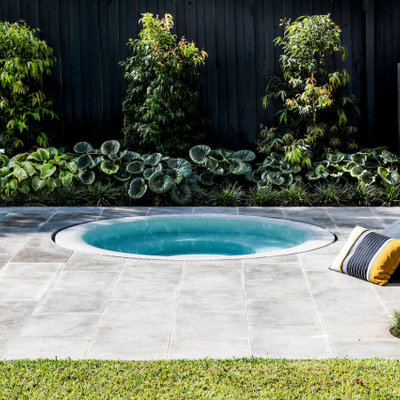 Example of a mid-sized minimalist backyard stone and custom-shaped pool landscaping design in Melbourne