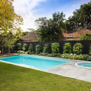 Réalisation d'une piscine arrière design de taille moyenne et rectangle avec un aménagement paysager autour d'une piscine et des pavés en pierre naturelle.