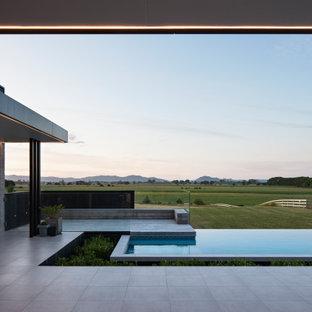 Ejemplo de piscina infinita, contemporánea, rectangular, en patio trasero
