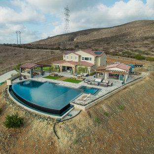 Foto de piscinas y jacuzzis infinitos, actuales, grandes, a medida, en patio trasero, con adoquines de piedra natural
