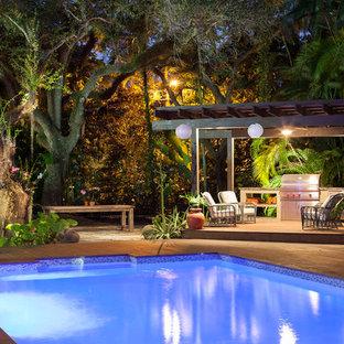 Diseño de piscina tropical, grande, en patio trasero, con entablado