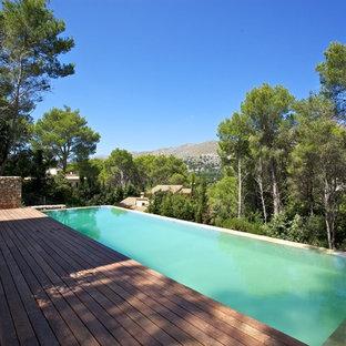 Ispirazione per una grande piscina a sfioro infinito rustica personalizzata sul tetto con pedane