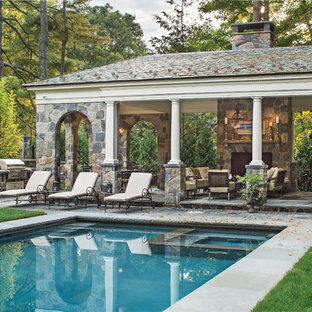 This is an example of an expansive traditional rectangular pool in New York with a pool house.