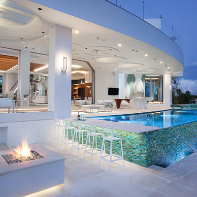 Example of a trendy backyard tile and custom-shaped infinity pool design