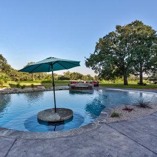 Ejemplo de piscinas y jacuzzis de estilo americano, extra grandes, a medida, en patio trasero, con suelo de hormigón estampado