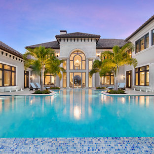 Expansive traditional backyard custom-shaped infinity pool in Miami with a water feature and natural stone pavers.