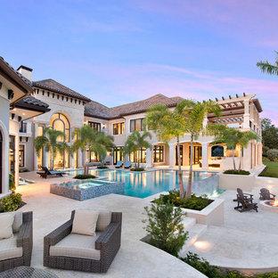 Foto di un'ampia piscina a sfioro infinito chic personalizzata dietro casa con fontane e pavimentazioni in pietra naturale