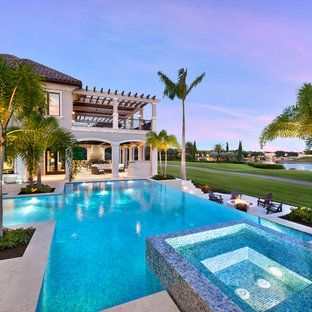 Inspiration for a huge timeless backyard stone and custom-shaped infinity pool fountain remodel in Miami