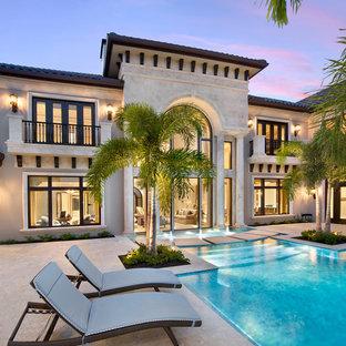 Geräumiger Klassischer Infinity-Pool hinter dem Haus in individueller Form mit Wasserspiel und Natursteinplatten in Miami