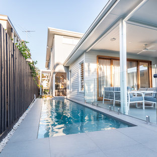 Mid-sized scandinavian side yard rectangular lap pool in Brisbane with concrete pavers.
