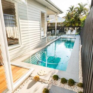 Idee per una piscina monocorsia scandinava rettangolare di medie dimensioni e nel cortile laterale con piastrelle