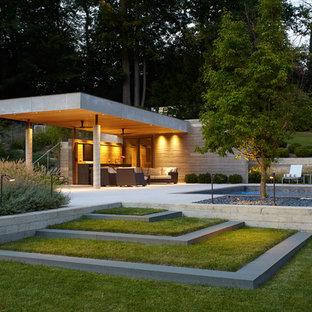 Immagine di una grande piscina minimalista rettangolare dietro casa con lastre di cemento