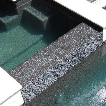 Gray Black Stone Pebble Flooring for a Pool Waterfall