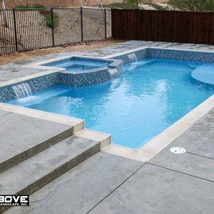 Foto de piscina tradicional, de tamaño medio, rectangular, en patio trasero, con suelo de hormigón estampado