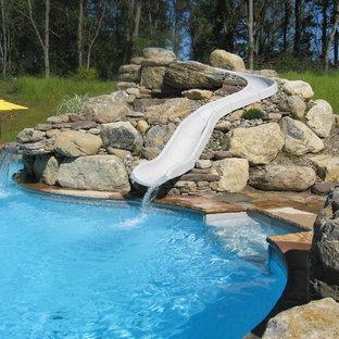Foto de piscina con tobogán natural, tradicional, grande, a medida, en patio trasero, con adoquines de piedra natural