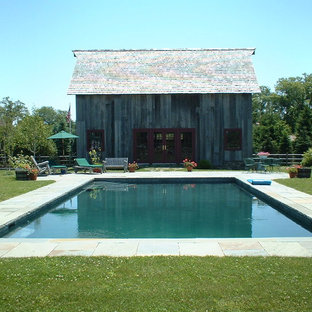 Large country backyard rectangular lap pool in New York with tile.