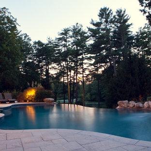 Идея дизайна: большой бассейн-инфинити произвольной формы на заднем дворе в стиле рустика с джакузи и покрытием из каменной брусчатки