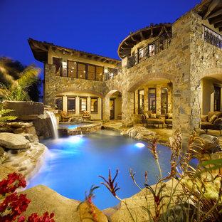 Imagen de piscina con tobogán tropical, a medida, en patio trasero, con suelo de hormigón estampado