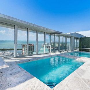 Modelo de piscina elevada, actual, grande, rectangular, en azotea, con privacidad y adoquines de piedra natural