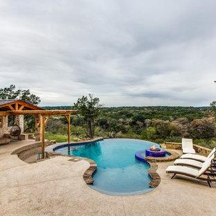 Ejemplo de piscina con fuente infinita, tradicional renovada, extra grande, a medida, en patio trasero, con suelo de hormigón estampado