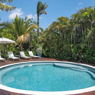 Foto de piscina exótica, redondeada, con entablado