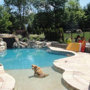 Immagine di una grande piscina naturale american style personalizzata dietro casa con un acquascivolo e pavimentazioni in cemento