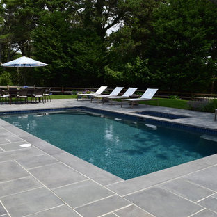 Example of a mid-sized beach style backyard tile and rectangular lap pool design in Boston