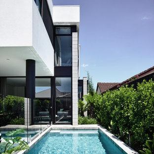 Diseño de piscina alargada, contemporánea, pequeña, rectangular, en patio trasero, con losas de hormigón