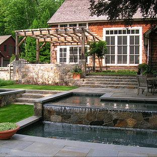 Diseño de piscina con fuente campestre, grande, rectangular, en patio trasero, con adoquines de piedra natural