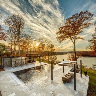 Cette image montre une grand piscine à débordement et arrière traditionnelle rectangle avec un bain bouillonnant et du carrelage.