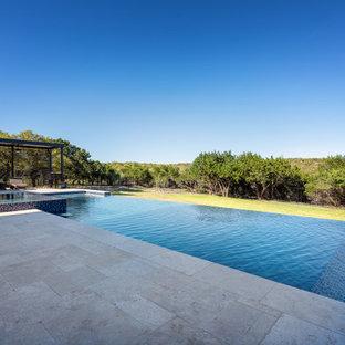 Réalisation d'une piscine à débordement et arrière minimaliste de taille moyenne et rectangle avec un aménagement paysager autour d'une piscine et des pavés en pierre naturelle.